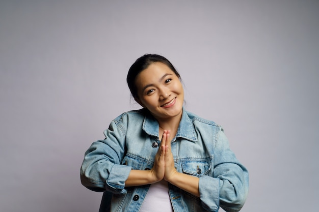 Азиатская женщина виновна, держась за руки в изолированном молитвенном положении.