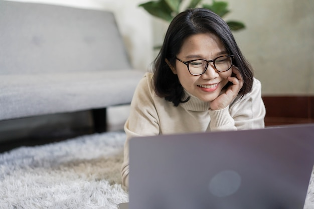Asian woman hand on chin while laying on rug and using laptop to surfing the internet concept