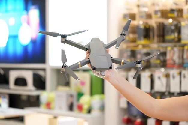 Азиатская женщина рука держит серый дрон в магазине электроники нерезкости.