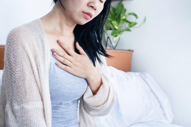 숨쉬기 힘든 가슴 통증을 안고 있는 아시아 여성