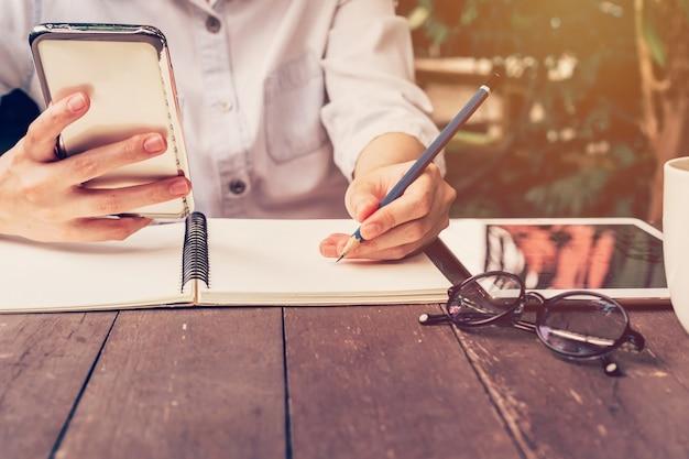 Азии женщина рука телефона и карандаш письменной записной книжки в кафе с урожай тонированное