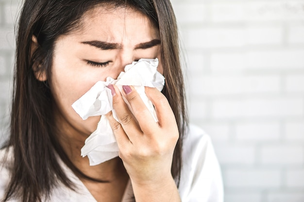 Asian woman hand holding tissue sneezing from flu