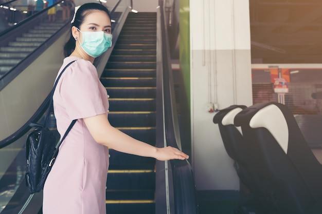 アジアの女性の手はエスカレーターの手すりを保持し、肘に咳をし、外科用フェイスマスクで他の人々との距離を保ちます-彼女はショッピングモールで通勤します