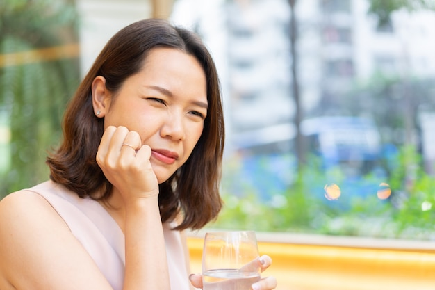 Asian woman  hand to massage cheek cause from toothache after drinking cold water for dental care