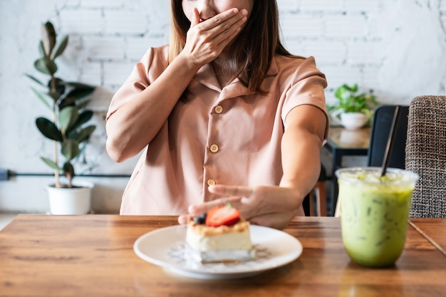 Азиатская рука женщины выталкивает нездоровую пищу. отказался от нездоровой пищи, здорового питания и диеты
