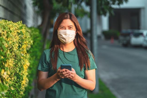 コロナウイルスを防ぐための安全医療フェイスマスク付きのスマート携帯電話を使用してアジアの女性の手