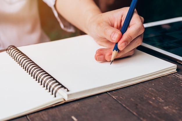 Азии женщина рука, писать карандаш на ноутбуке в кафе с урожай тонированные
