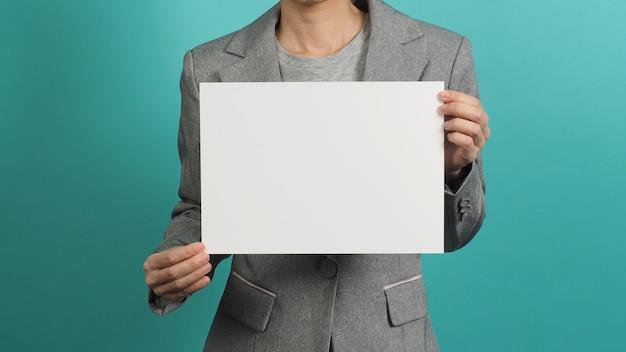 아시아 여성은 빈 종이 보드를 들고 파란색 또는 민트 배경에 격리된 회색 양복을 입고 있습니다.