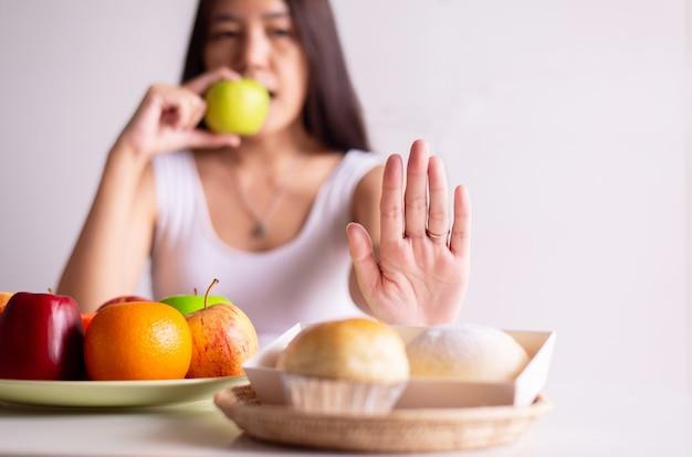 アジアの女性の手はパンに停止し、白い背景、健康的な食事、ダイエットの概念に青リンゴを保持します。