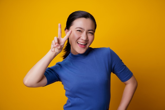 Asian woman happy cheerful showing peace sign with two fingers on yellow.