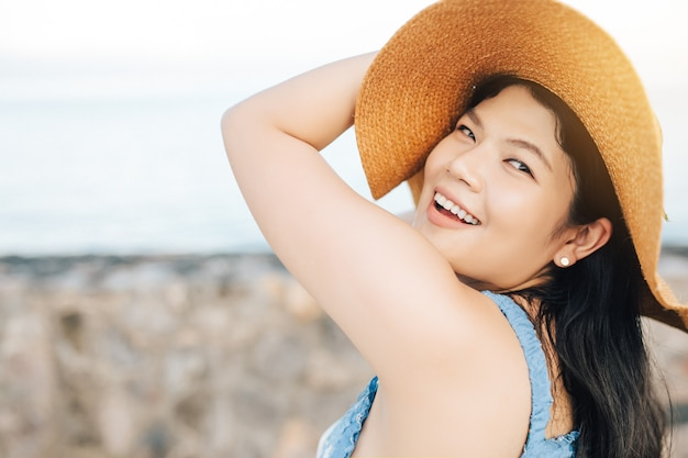 Asian woman happy smiling girl enjoying the beach and looking at camera in summer