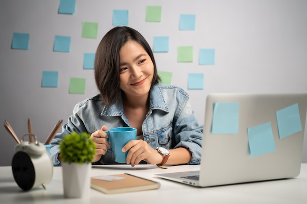 ノートパソコンを見て、ホームオフィスでニュースを読んで幸せな笑顔のアジアの女性。在宅勤務。予防コロナウイルスcovid-19コンセプト。