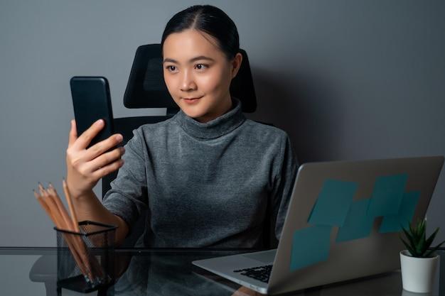 Азиатская женщина счастлива улыбается с помощью смартфона и работает на ноутбуке в офисе