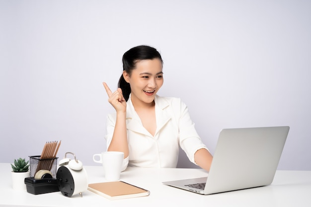 Asian woman happy smiling in white shirt working on a laptop at office. isolated on white background.