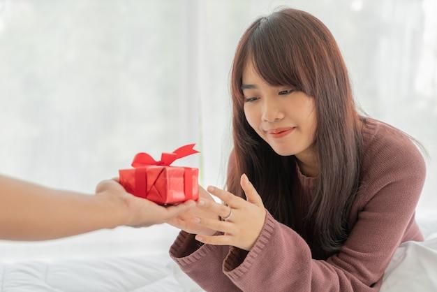 Азиатская женщина счастлива получить подарочную коробку