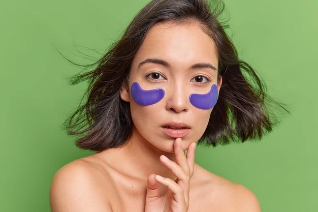 La donna asiatica ha i capelli scuri che fluttuano nell'aria applica cerotti idrogel blu sotto gli occhi si sottopone alla cura della pelle