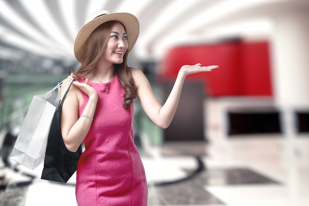 Asian woman in hat holding shopping bags in the mall
