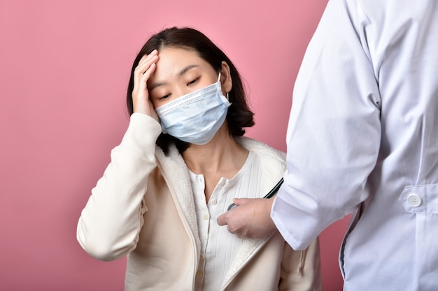 Asian woman have sore throat allergy and coughing in face mask, sneezing and coughing spread coronavirus disease droplet, doctor screening covid-19 infected patient in hospital.