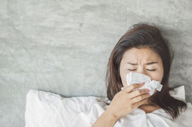 Asian woman having flu and sneezing on bed