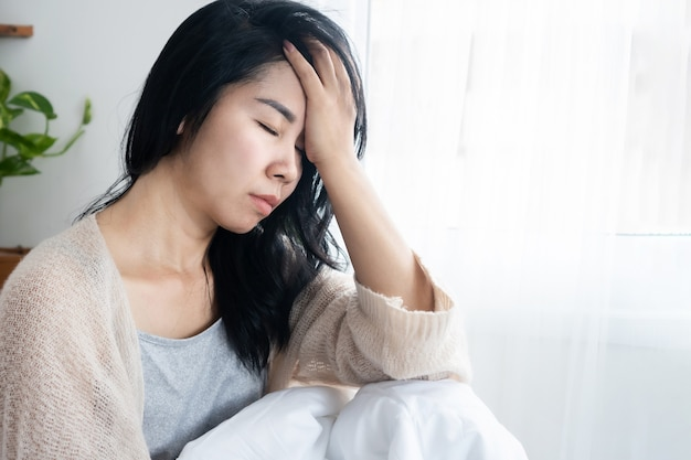 Asian woman having headache migraine lack of sleep after wake up in the morning