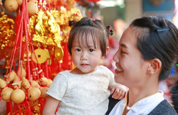 Asian woman and her daughter in chinese dress against traditional chinese red decorations