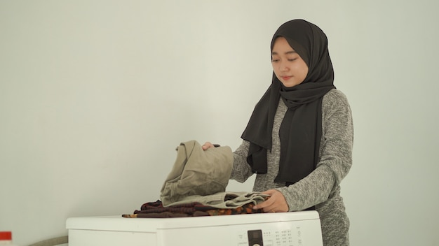 Asian woman in hijab folds washed clothes at home
