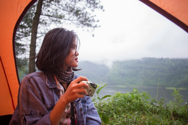 アジアの女性ハイカーは、カメラで自然の美しさを楽しんで、幸せを感じます