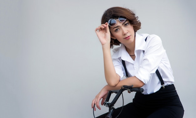 Asian woman in hipster casual dress posting on a bicycle holding her glasses with white background.