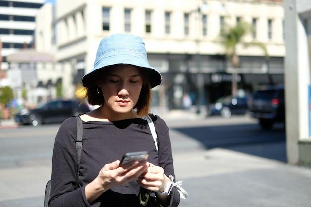 アジアの女性の流行に敏感な旅行と街で携帯電話を使用しています。