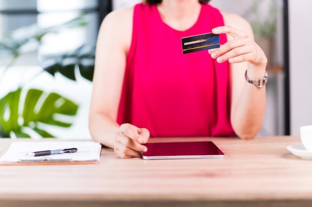 아시아 여성은 지갑 앱 기술로 태블릿 결제를 위한 신용 카드를 보유하고 있습니다. 태블릿 응용 프로그램, 은행 및 전자 상거래 개념으로 지불하고 쇼핑하는 여성.