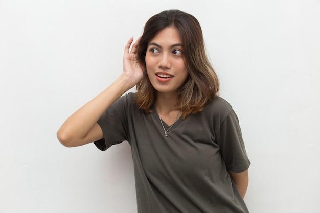 Азиатская женщина держит руку возле уха и слушает