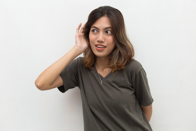 Asian woman hold her hand near her ear and listening