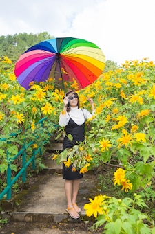 Asian woman hold multicolor umbrella.