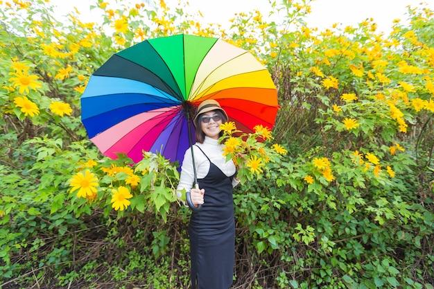 Asian woman hold multicolor umbrella.