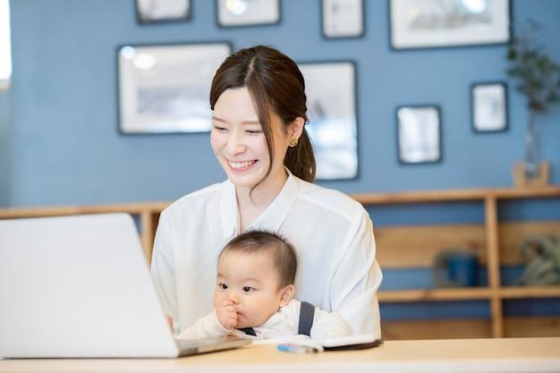 赤ちゃんを抱いて、屋内でラップトップを操作するアジアの女性