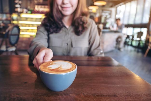 카페에서 나무 테이블에 라떼 아트와 함께 뜨거운 라떼 커피의 파란색 컵을 들고 아시아 여자