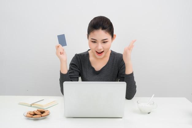 Азиатская женщина держит кредитную карту и делает покупки в интернете