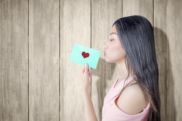 Азиатская женщина, держащая зеленый конверт с сердцем с деревянной предпосылкой. день святого валентина