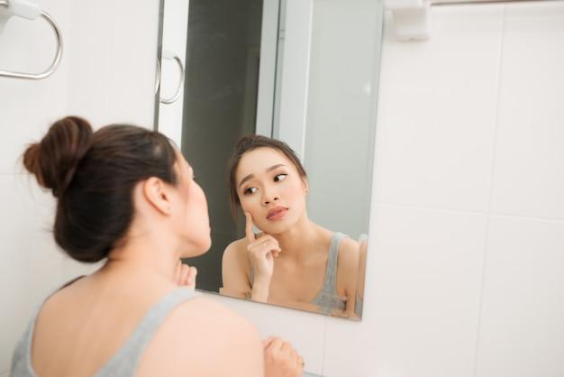 鏡を持って、触れて、彼女の顔を心配しているアジアの女性