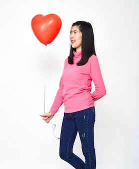 Asian woman holding a red heart balloon