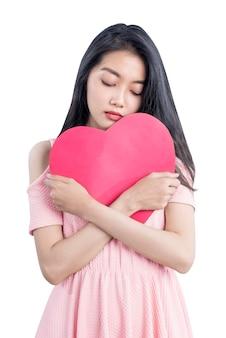 흰색 배경 위에 절연 슬픈 표정으로 빨간 하트를 들고 아시아 여자