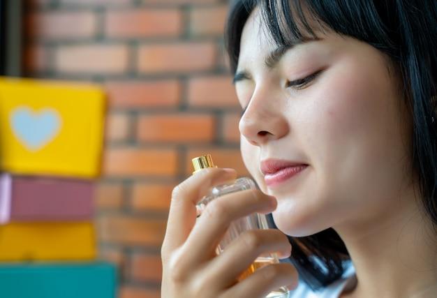 小瓶を持って香水の臭いがするアジアの女性。