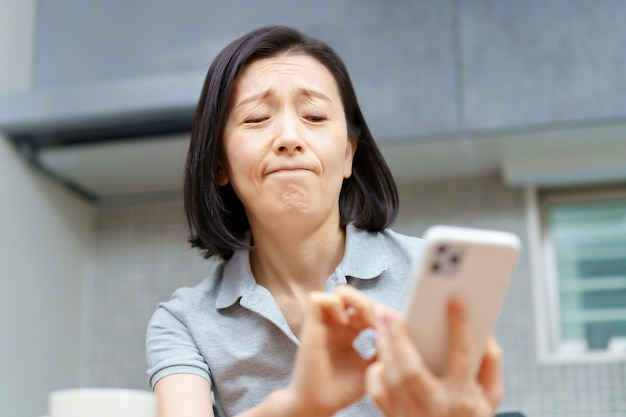 방에 피곤한 표정으로 스마트 폰을 들고 아시아 여자