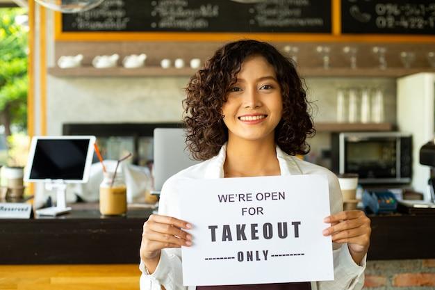 고객에게 알리기 위해 a4 용지를 들고 있는 아시아 여성은 음식 테이크아웃만 주문하기 위해 옵니다.