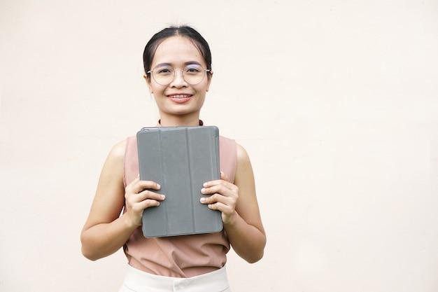 Азиатская женщина держит ipad для бизнеса через приложение