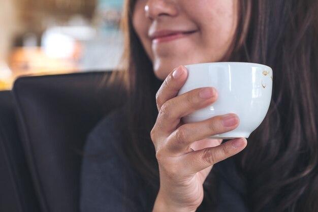 Азиатская женщина холдинг и пить кофе
