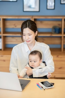 Asian woman holding a baby and operating a laptop indoors