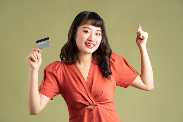 Asian woman holding a bank card and showing victory emotion