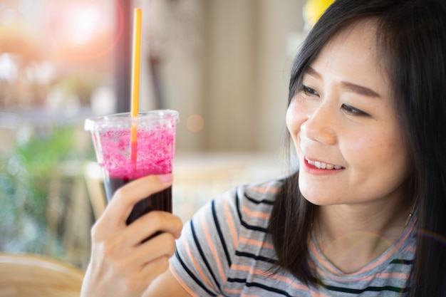Asian woman holding a beetroot juice with happy, concept in eating healthy.
