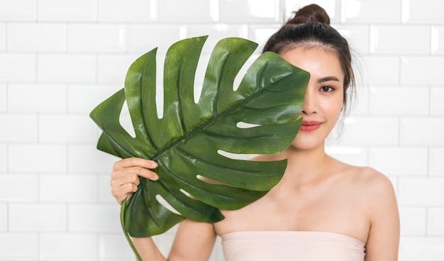 白いレンガの壁の背景と彼女の顔に大きな葉を保持しているアジアの女性